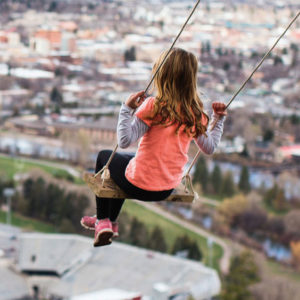 girl on swing overlooking city