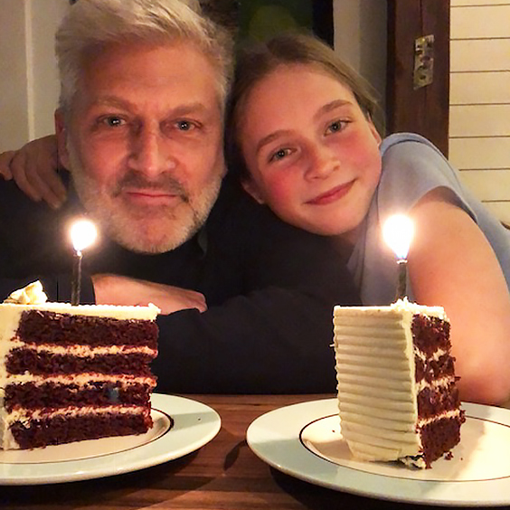 Jack Lawson and daughter smiling in front of two pieces of birthday cake.