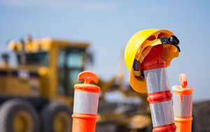 Construction cones with hard hat sitting on top. Construction equipment in background.