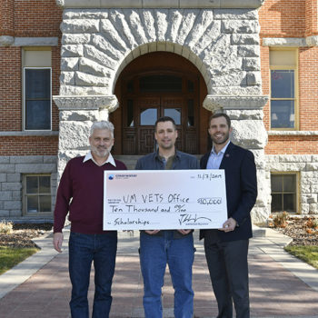Photo of three men standing with a donation check of $10,000 at the University of Montana.