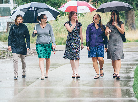 Photo of a group of women in the Women's Leadership Initiative walking with umbrellas on the University of Montana campus.