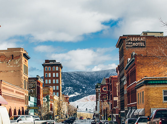 Photo of snow Uptown Butte, Montana with parked vehicles and historic buildings on either side of the street.