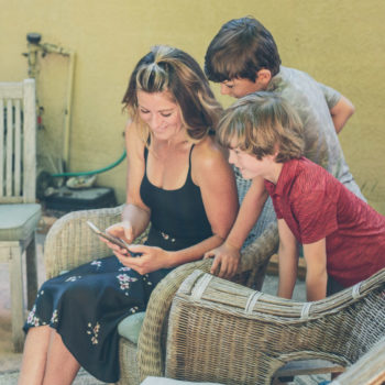 Photo of Clearwater member, Kristina, checking her mobile banking app with her two young boys looking over her shoulder sitting outside.