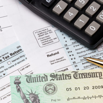 Photo of calculator, pen, tax documents, and a tax refund check on a desk.