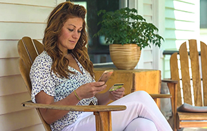 Photo of member, Kristina, sitting on her front porch looking at her phone with her debit card in the other hand.