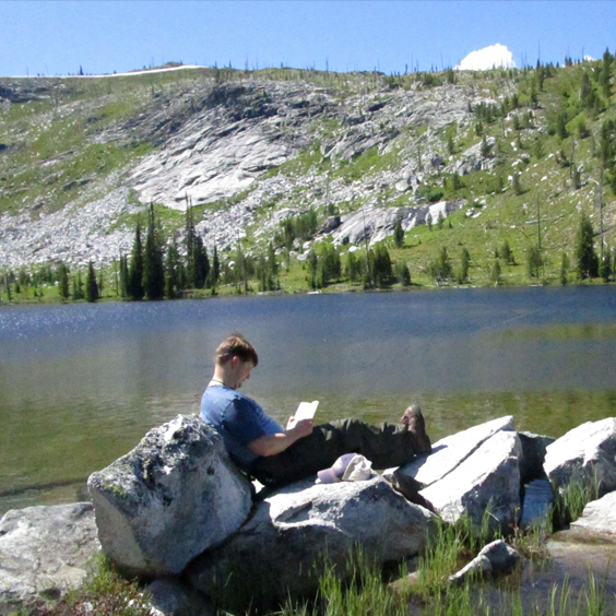 John De Groot, Chief Financial Officer, Clearwater Credit Union. Photo of him reading by a lake in the mountains.