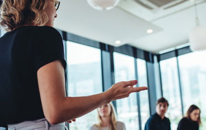 Woman presenting to meeting room of people.
